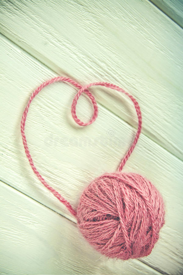 Knitting yarn rolled into heart ball. On a white wooden background stock image