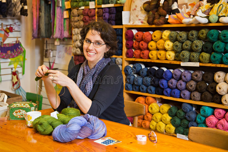 Knitting in a yarn shop. Beautiful brunette knitting at a work table in a yarn shop