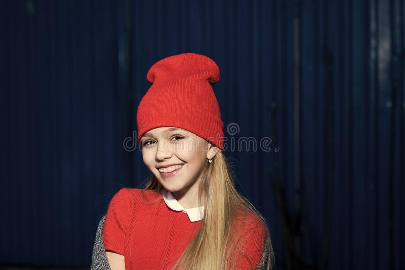 knitwear Niño que sonríe con el pelo rubio largo al aire libre, belleza Pequeña sonrisa en sombrero rojo, moda de la muchacha Ten fotos de archivo