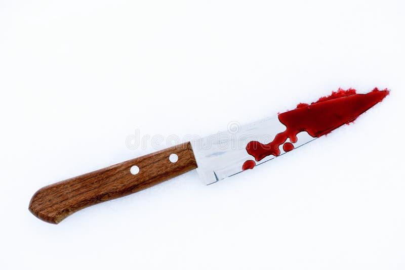 Kniv för mordvapen med blod Splats och droppar på snö royaltyfri foto