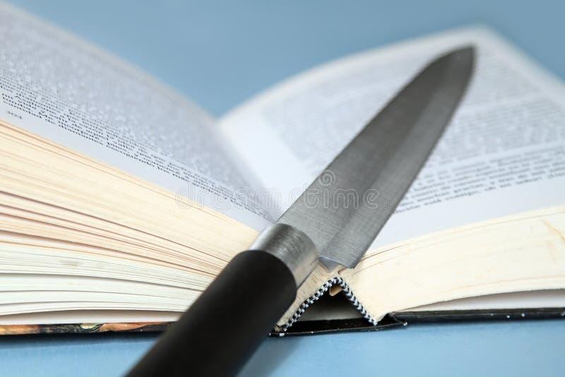 Kniv och bok arkivbild