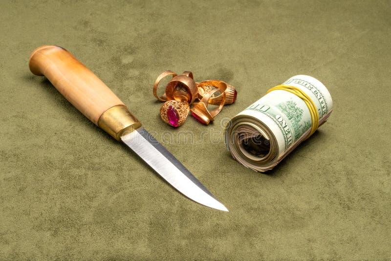 Kniv och dollar och guld på en grön bakgrund royaltyfria bilder