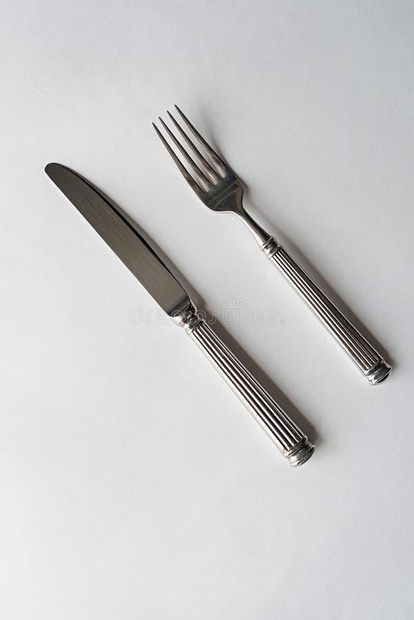 Kniv och gaffel p? en vit bakgrund arkivbild