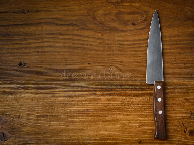Kniv på det lantliga köksbordet med kopieringsutrymme royaltyfria foton