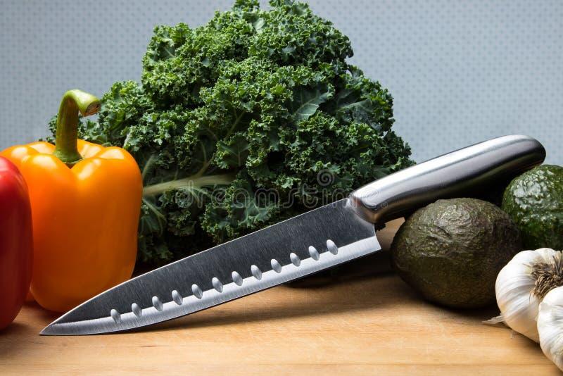 Kniv på skärbräda med grönsaker arkivfoton