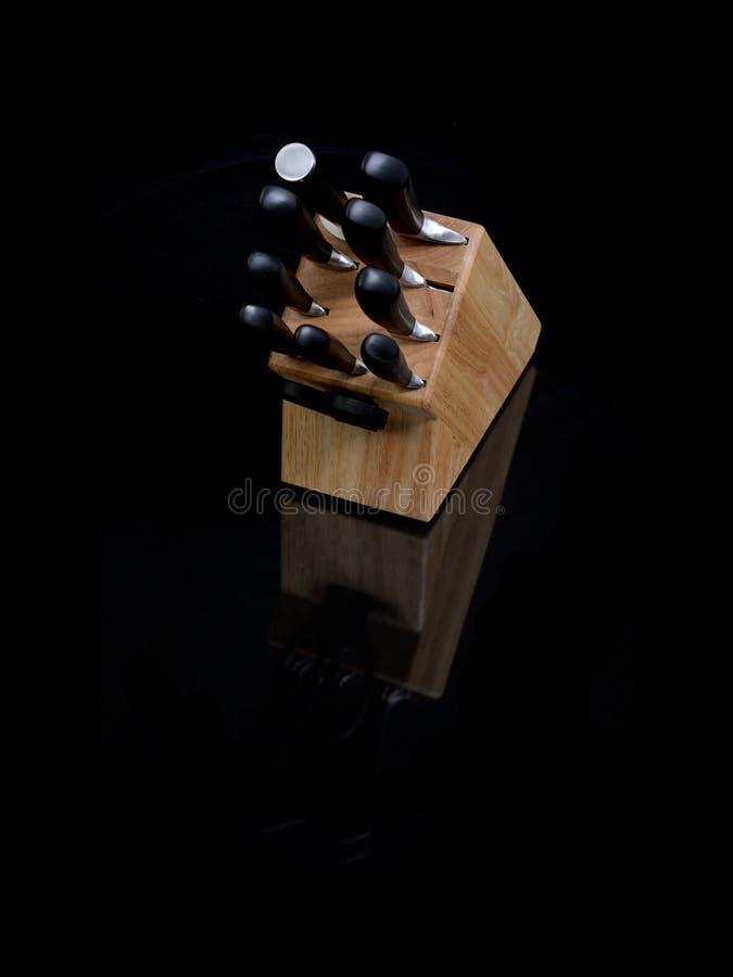 Knivar i trähållare på svart royaltyfri foto