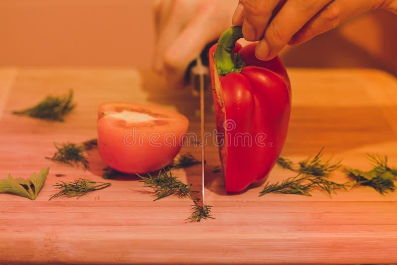 Kniven klipper röd peppar och en tomat som ligger bredvid den gröna dillen och persiljan royaltyfri foto