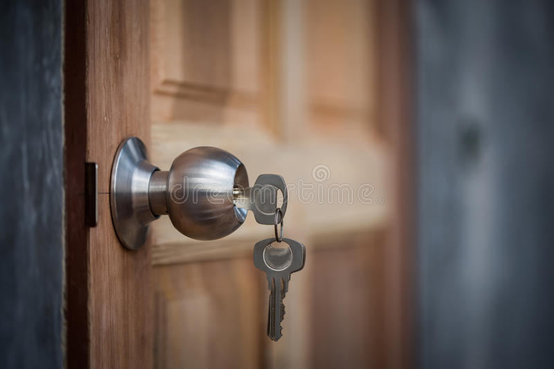 Knob, key and wooden door on gray background stock images