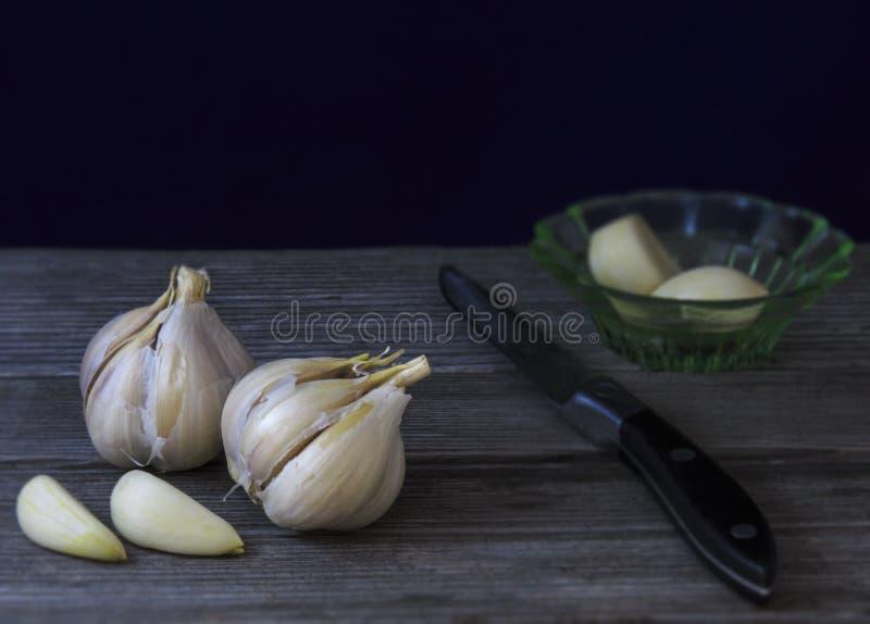 Knoblauch, Messer, Untertasse auf einem Holztisch stockfotografie