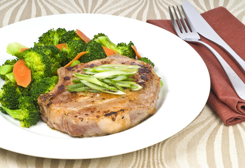 Knoblauch-Schweinekotelett und Brokkoli stockfoto