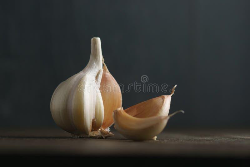 Knoblauch und Knoblauchzehen auf Dunkelheit lizenzfreies stockbild