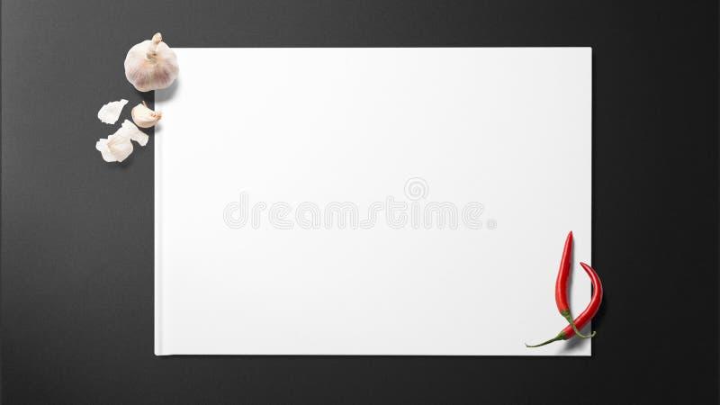 Knoblauch und Paprikas auf Weißbuch auf schwarzem Hintergrund stockfotos