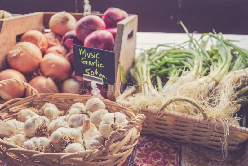 Knoblauch und Zwiebeln für Verkauf in den Körben am Landwirt ` s Markt für Fall ernten stockfoto
