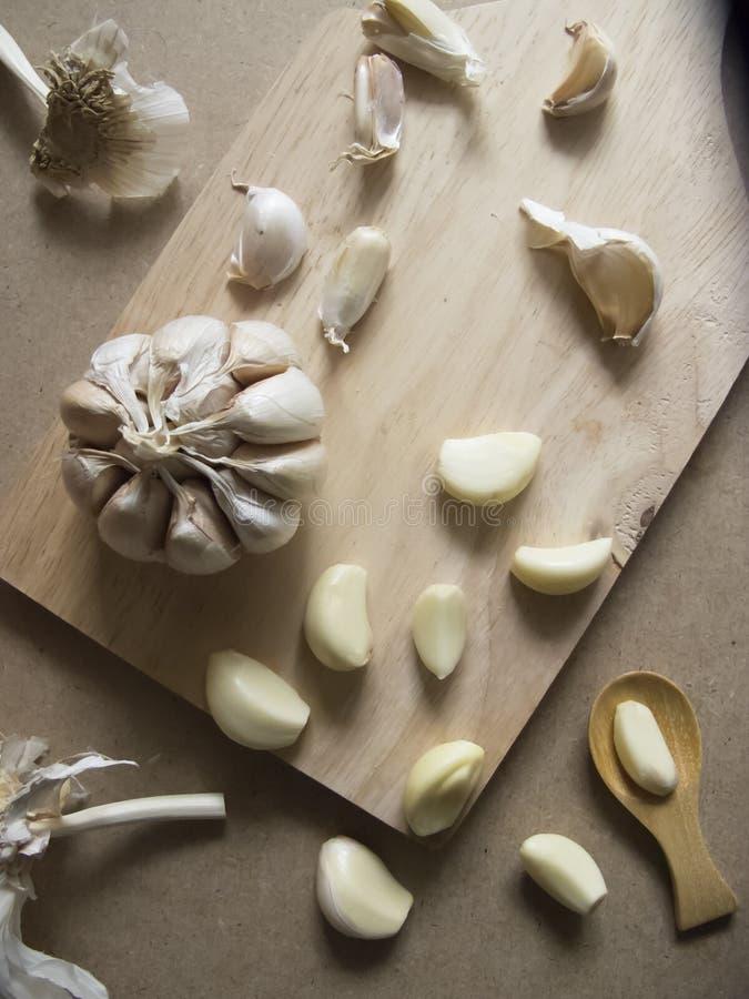 Knoblauchknolle und Knoblauchzehen auf dem hölzernen Hacken lizenzfreies stockfoto