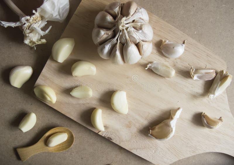 Knoblauchknolle und Knoblauchzehen auf hölzernem hackendem Brett stockfotografie