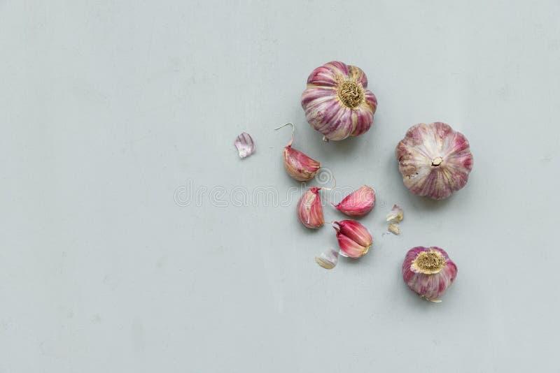 Knoblauchknollen und Nelken auf grauem hölzernem Hintergrund Herbstblattrand mit verschiedenem Gem?se auf wei?em Hintergrund Besc stockfotografie