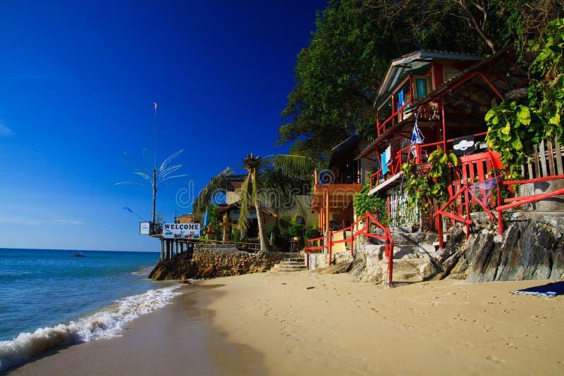 KNOCK-OUT CHANG, THAILAND - DECEMBER 7 2018: Weergeven op wit zandstrand met groene bomen en kleurrijke houten huizen stock afbeelding