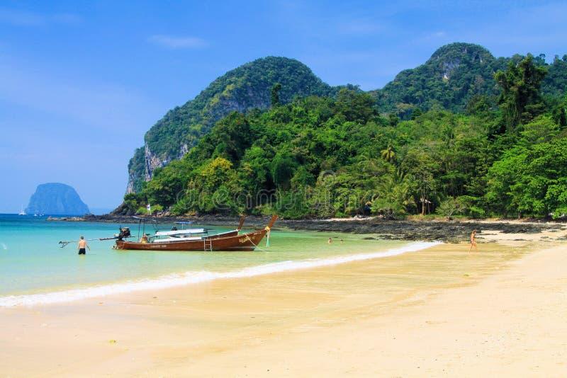 KNOCK-OUT MOK, THAILAND ANDAMAN-HAV - DECEMBER 28 2013: Fartyg för lång svans i paradislagun med gröna berg royaltyfria foton