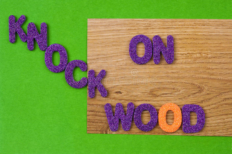 Knock on Wood in purple characters on paper. Superstition: The words KNOCK ON WOOD in glittering, purple, plastic characters on green paper and on paper with a royalty free stock image