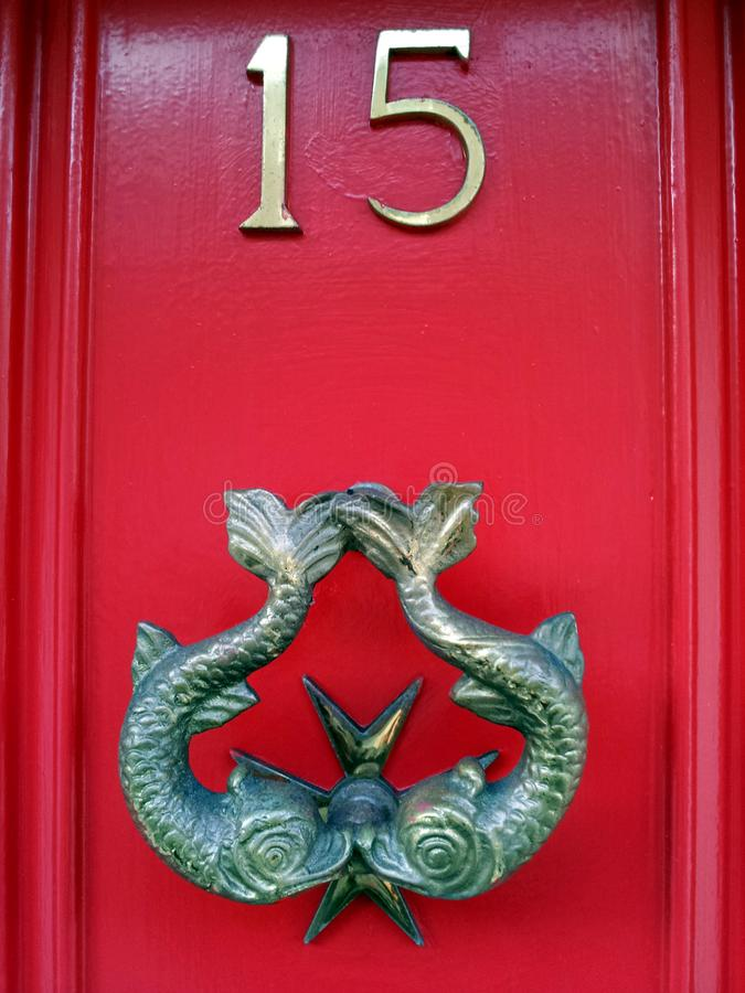 Knocker on red door number 15 with Pisces fish royalty free stock images