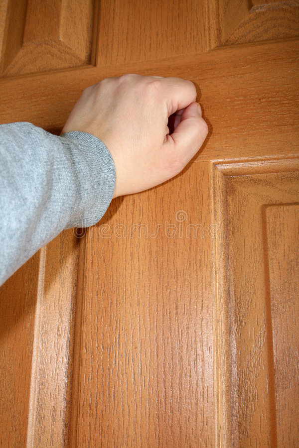 Knocking. A hand knocking on a door stock image