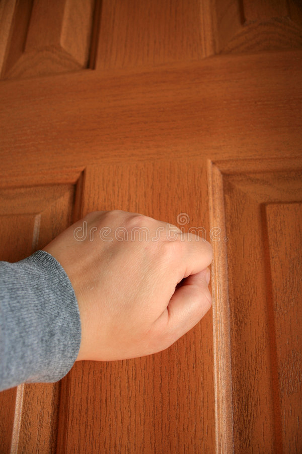 Knocking. A hand knocking at a door that has a cross shape on it stock photo