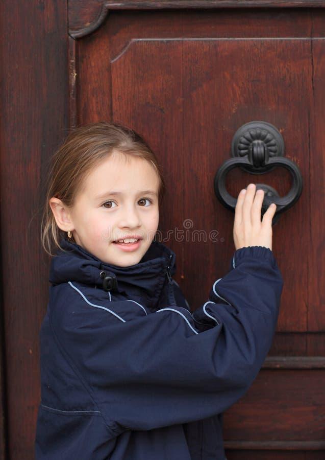 Knocking on door. Little girl knocking on heavy wooden door with knocker stock photo