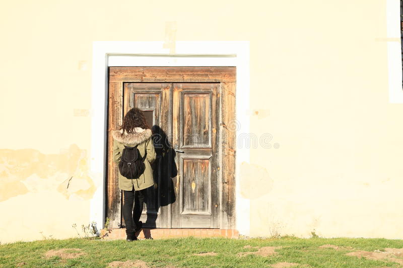 Knocking on door. Young woman - girl knocking on wooden door royalty free stock photos