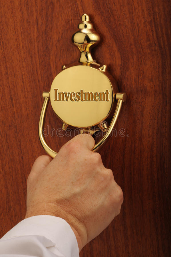 Knocking on home investment. Hand of person knocking on retro doorknob with word investment; home or property investment concept stock images