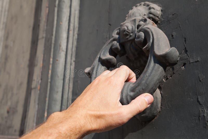 Knocking old black door with metal ring knocker. Male hand knocking old black door with metal ring knocker stock photos