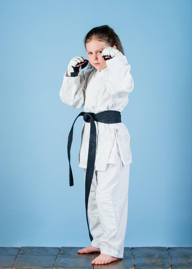 knockout Energie und T?tigkeit f?r Kinder kleines M?dchen in der Kampfkunstuniform ?bendes Kung Fu Gl?ckliche Kindheit sport lizenzfreies stockfoto