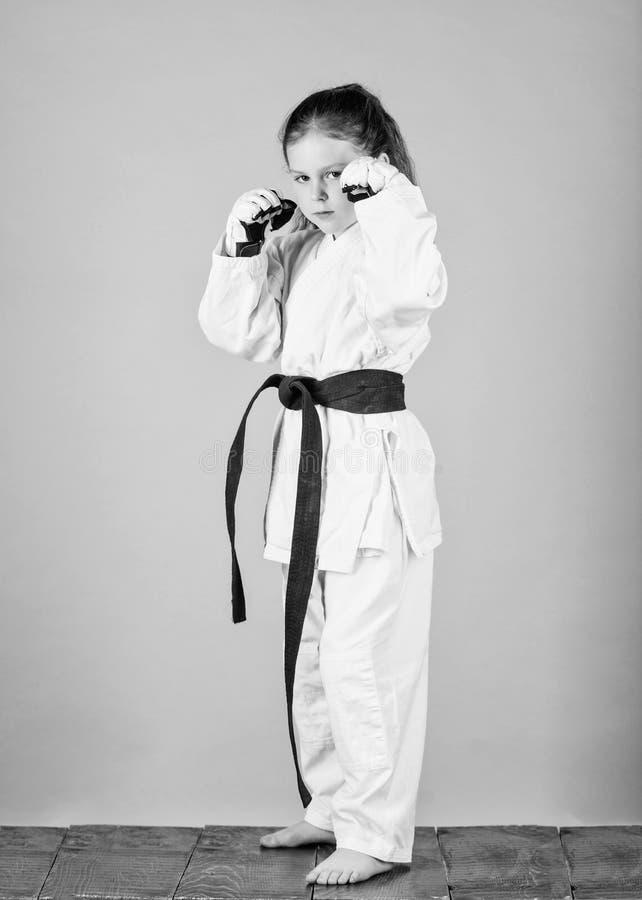 knockout Energie und T?tigkeit f?r Kinder kleines M?dchen in der Kampfkunstuniform ?bendes Kung Fu Gl?ckliche Kindheit sport stockfotos