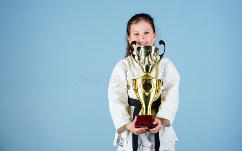 knockout Energie und T?tigkeit f?r Kinder kleines M?dchen des Siegers in der Gisportkleidung kleines M?dchen mit Meistercup -M?dc stockfotografie