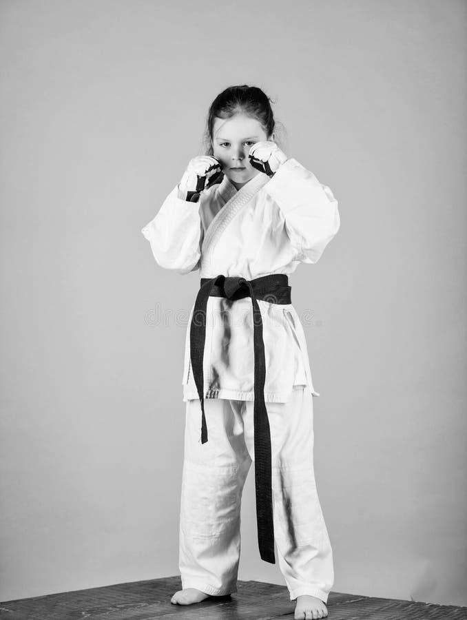 knockout Energie und T?tigkeit f?r Kinder wenig M?dchen in der Gisportkleidung kleines M?dchen in der Kampfkunstuniform ?ben lizenzfreies stockbild