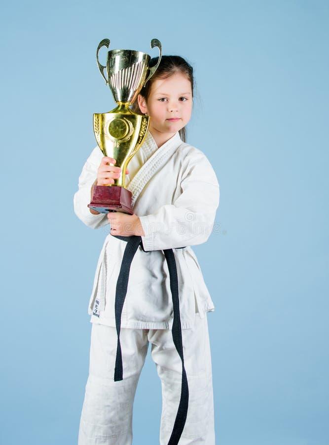 knockout Energiet?tigkeit f?r Kinder kleines M?dchen mit Meistercup chinesische KONGFU Kinder Praxis Kung Fu Gl?ckliche Kindheit  stockfotografie