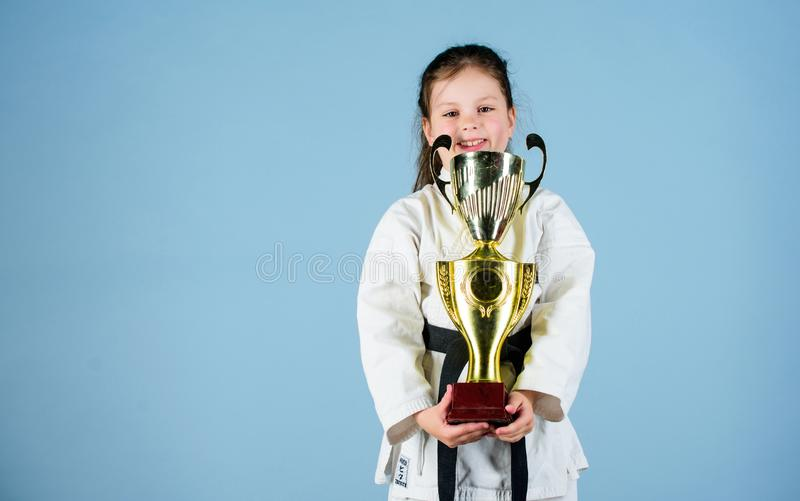 Knockout. energy and activity for kids. winner little girl in gi sportswear. small girl with champion cup. martial art. Practicing Kung Fu. happy childhood stock photography