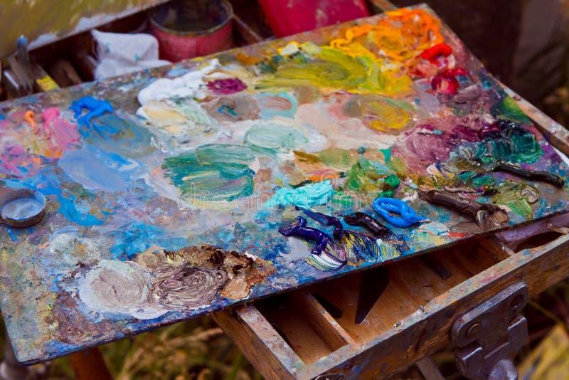Knoeit het houten die palet van de schilder met wordt bevlekt van verse gemengde kleurrijke olieverven, rust op schildersezel royalty-vrije stock afbeelding