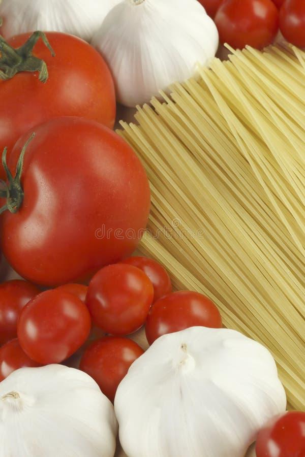 Knoflook, deegwaren en tomaten stock afbeelding