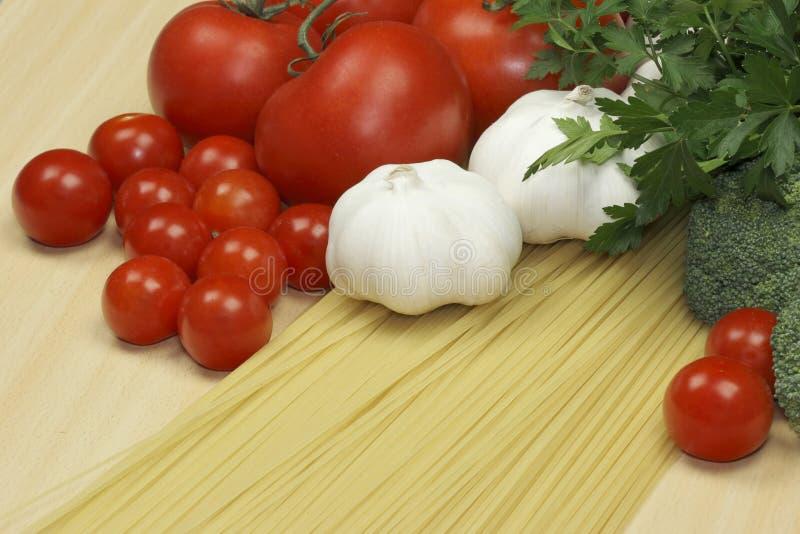 Knoflook, deegwaren en tomaten stock foto