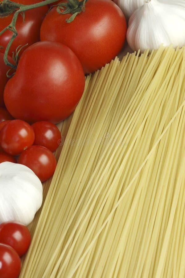 Knoflook, deegwaren en tomaten stock foto's