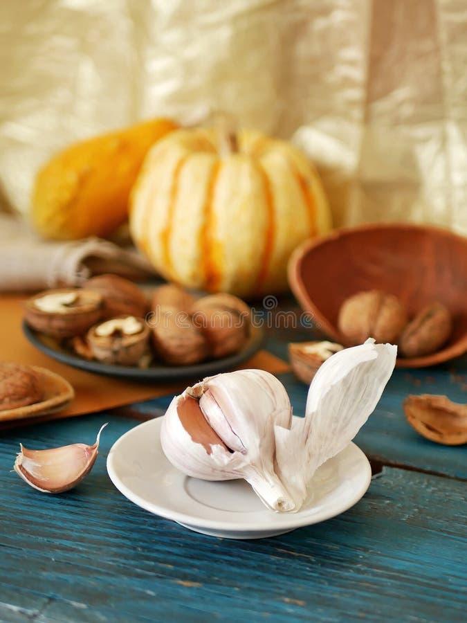 Knoflook, okkernoten, groenten op een houten lijst, ingrediënten voor het voorbereiden van gezond organisch voedsel, seizoengebon stock foto