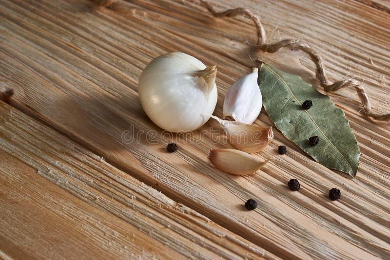Knoflook, ui, laurierblad, zwarte peper op een houten lijst De achtergrond van het voedsel garlics gesneden knoflook, knoflookkru stock afbeelding