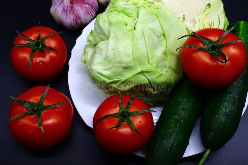 Knoflook, witte kool, rode tomaten en twee komkommers in een witte plaat op een zwarte achtergrond stock foto