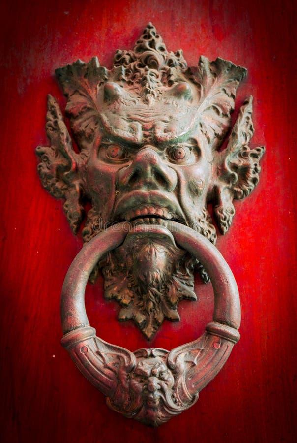 Knoker della porta su una vecchia porta di legno rossa immagini stock
