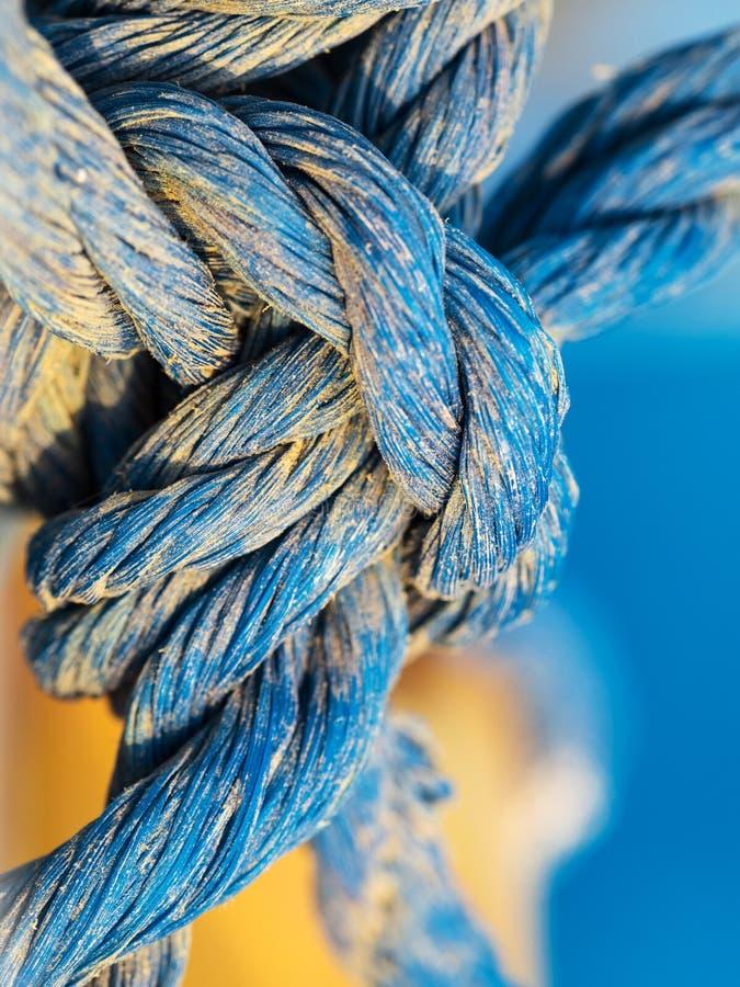 Knoop van blauwe verdraaide kabel in de korrels van zand in detail wordt gemaakt, marien concept, macro die stock afbeeldingen