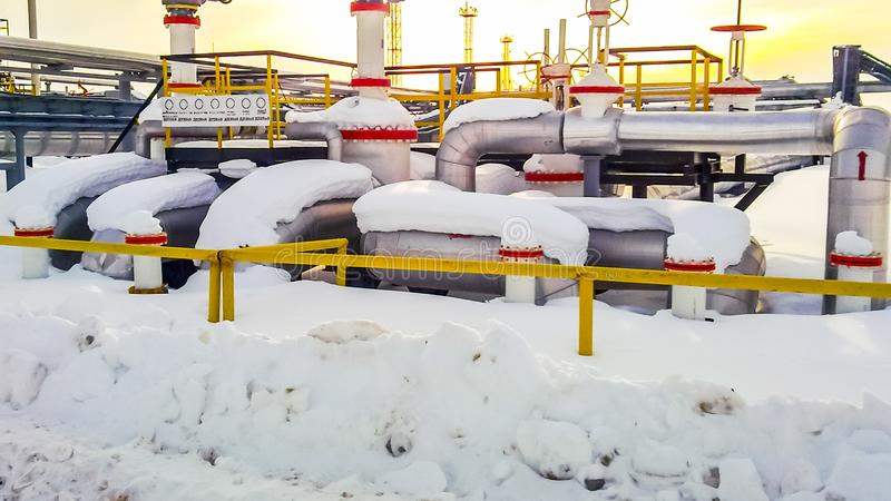 Knoop van kleppen op oliepijpleidingen Sluitkleppen in de sneeuw Reductiemiddelen op de kleppen stock afbeeldingen