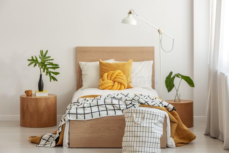 Knoophoofdkussen en zwart-witte deken op eenpersoonsbed in modieus binnenland met groen blad in vaas op houten nightstand stock fotografie