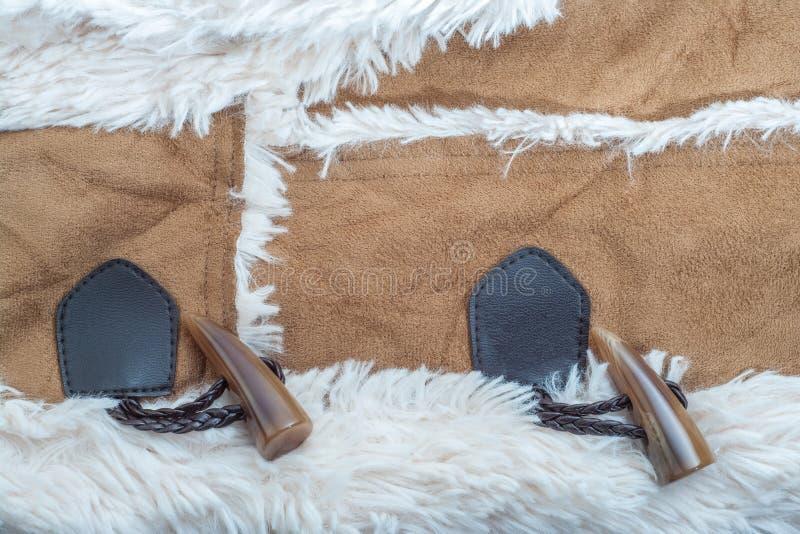 Knoopt het textuur beige suède met kunstmatige zachte bont en knevel vastmakende close-up dicht royalty-vrije stock foto's