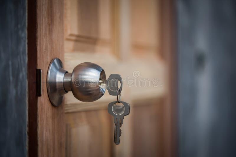Knop, zeer belangrijke en houten deur op grijze achtergrond stock afbeeldingen