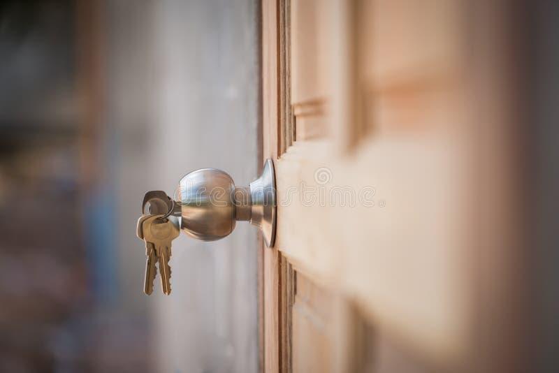 Knop, zeer belangrijke en houten deur op grijze achtergrond royalty-vrije stock fotografie